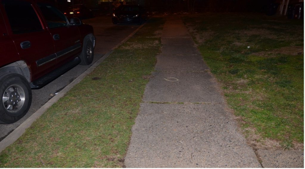 Sidewalk in front of 3207 W. 2nd Street. The spent shell casing from M/Cpl. David Simmons is in the yellow circle.