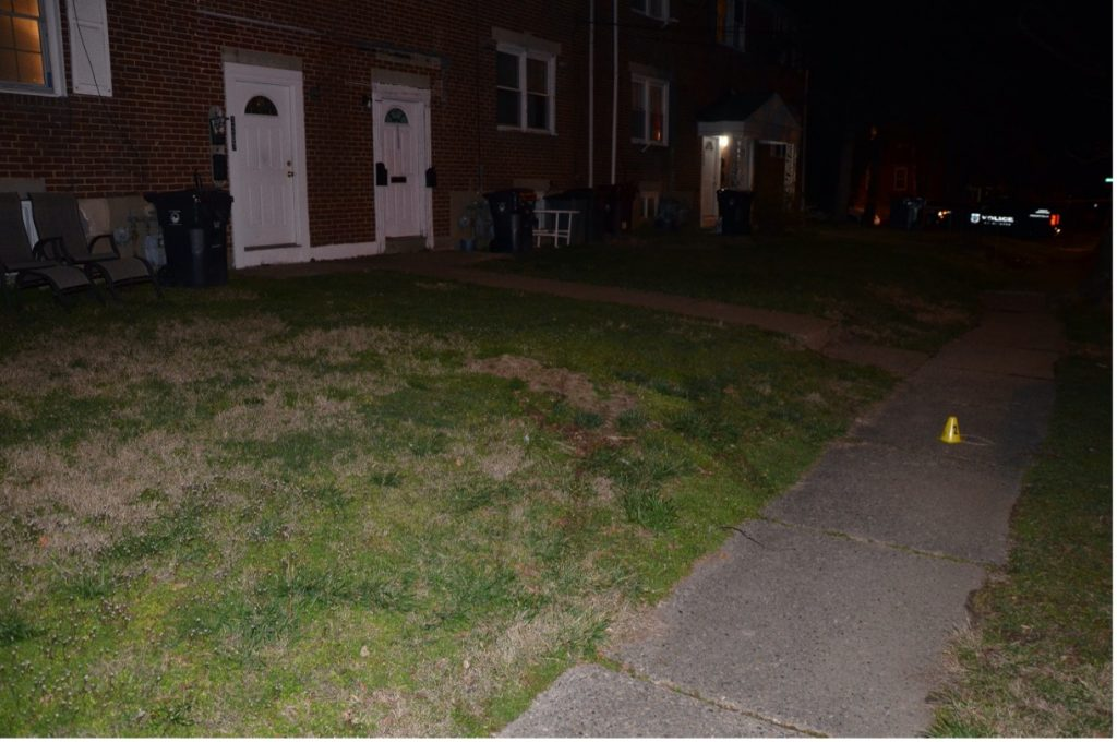 Front yard of 3207 W. 2nd Street. The yellow cone depicts M/Cpl. Simmons' shell casing. Vehicle marks can be seen in the grass. M/Cpl. Simmons was standing in the area of the sidewalk when he discharged his weapon.