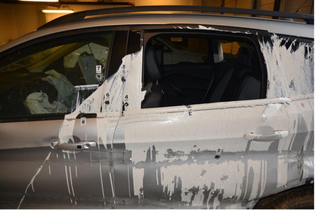Bullet holes in the driver side of the stolen car, from the police case. The white paint did not occur during the police chase.