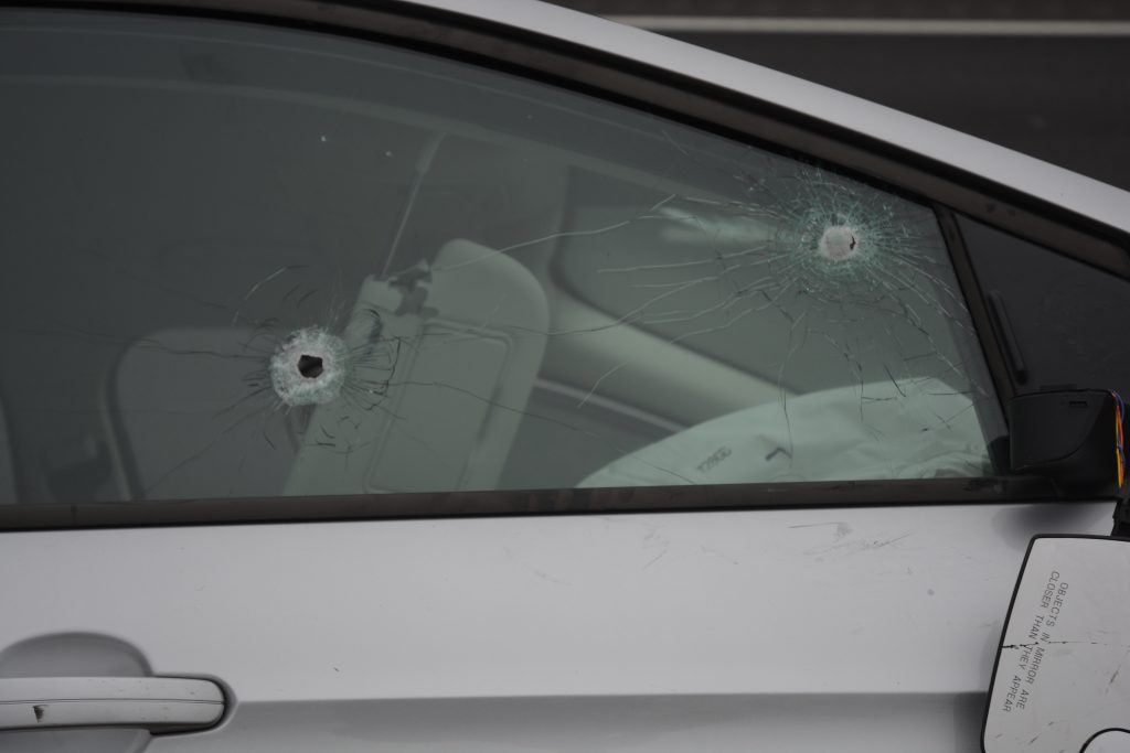 Bullet holes in the passenger side window of the stolen car.