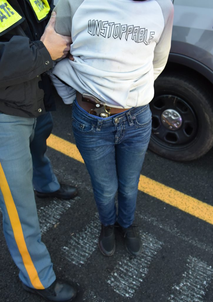 Revolver in the pants of the 13-year-old suspect, standing with Delaware State Police.The Delaware State Police noticed the firearm prior to their transport of the suspect and took this photograph